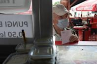 Titei Constantin, 77, holds a voucher for 3 mici received after being vaccinated, in Bucharest