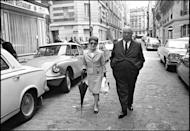 """<p>The """"Master of Suspense""""—and brains behind iconic spooky movies like <em>Psycho</em> and <em>The Birds</em>—tours Paris with his wife, Alma Reville.</p>"""
