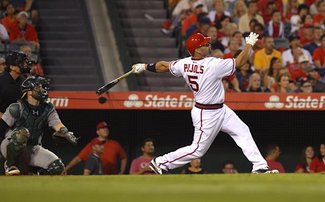 Los Angeles Angels' Albert Pujols follows through on a solo home run in front of Oakland Athletics catcher Derek Norris during the seventh inning of a baseball game, Friday, Aug. 29, 2014, in Anaheim, Calif. (AP Photo/Mark J. Terrill)