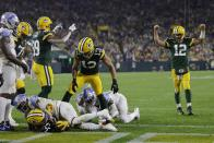 Green Bay Packers' Aaron Rodgers celebrates a touchdown run by Aaron Jones during the second half of an NFL football game against the Detroit Lions Monday, Sept. 20, 2021, in Green Bay, Wis. (AP Photo/Mike Roemer)