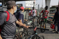 Men wearing protective masks push their bicycles at an overpass in Quezon city, Philippines, Saturday Sept. 26, 2020. Public transportation remains limited and the government orders commuters to wear face shields and face masks to help curb the spread of the coronavirus. (AP Photo/Aaron Favila)