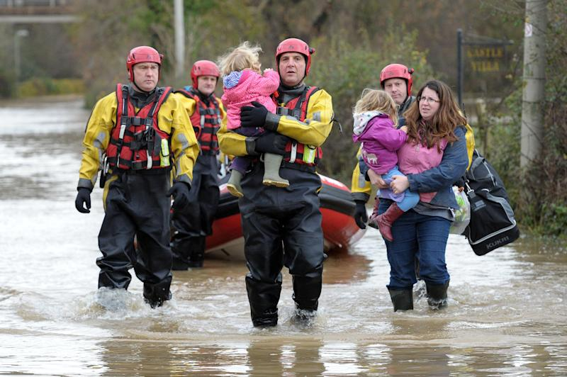 Crew Commander from Tewkesbury fire station Dave Webb carries 19-month-old daughter of Tina Bailey who carries her 3 year old daughter, after they were rescued from their house in Gloucester, England, Tuesday Nov. 27, 2012. Thousands of drivers and residents face further chaos today after heavy rain continued to fall across Britain overnight. (AP Photo/PA, Tim Ireland) UNITED KINGDOM OUT NO SALES NO ARCHIVE