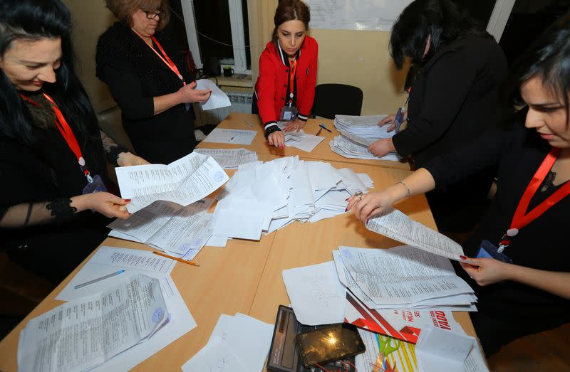 Members of a local electoral commission count ballots at a polling station after a snap parliamentary election in Baku