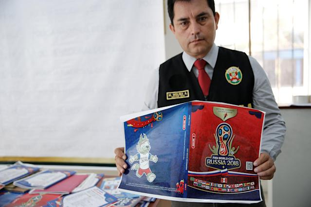 A Peruvian police official shows counterfeit World Cup sticker books seized during a police operation in Lima, Peru April 18, 2018. REUTERS/Janine Costa