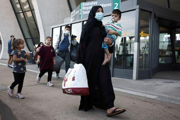 <strong>A family evacuated from Kabul Afghanistan walks through the arrival terminal Dulles International Airport.</strong> (Photo: Anna Moneymaker via Getty Images)