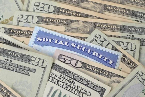 A Social Security card nestled among many U.S. currency bills
