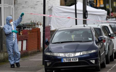 A forensic investigator stretches police tape across Chalgrove Road, where a teenage girl was murdered, in Tottenham, Britain, April 3, 2018. REUTERS/Toby Melville