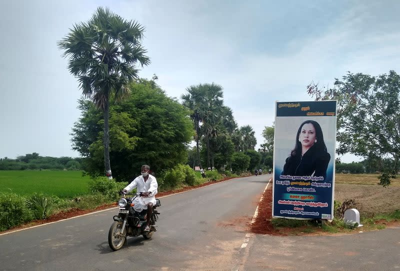 A man drives past a banner of U.S. Democratic vice presidential nominee Kamala Harris at the entrance to the village of Thulasendrapuram
