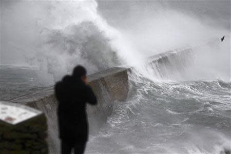Waves crash over the breakwater of Saint Evette harbour at Esquibien in Brittany as an Atlantic storm hits western France, December 23, 2013. REUTERS/Mal Langsdon
