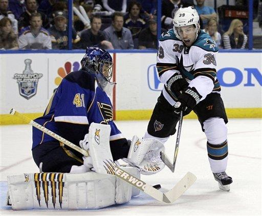 San Jose Sharks' Logan Couture, right, tries to reach a loose puck as St. Louis Blues goalie Jaroslav Halak, of Slovakia, defends during the first period in Game 2 of an NHL Stanley Cup first-round hockey playoff series Saturday, April 14, 2012, in St. Louis. (AP Photo/Jeff Roberson)