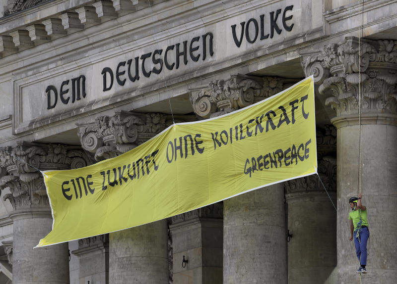 Activists of Greenpeace extendet the inscription 'Dem deutschen Volke' (To the German People) on top of the entrance of the Reichstag building, home of the German parliament Bundestag, with the slogan 'Eine Zukunft Ohne Kohlekraft' (a future without coal power) in Berlin, Germany, Friday, July 3, 2020. (AP Photo/Michael Sohn)