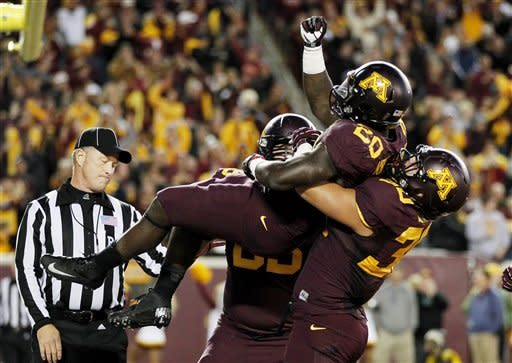 Minnesota running back Donnell Kirkwood (20) celebrates with teammates after scoring a touchdown in the first half of an NCAA college football game against Syracuse in Minneapolis, Saturday, Sept. 22, 2012. (AP Photo/Andy King)