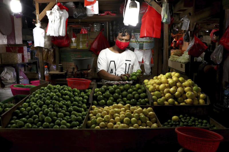 A fruit vendor wears a face mask as a precaution against the new coronavirus at his stall in a traditional market in Jakarta, Indonesia, Tuesday, June 2, 2020. (AP Photo/Tatan Syuflana)