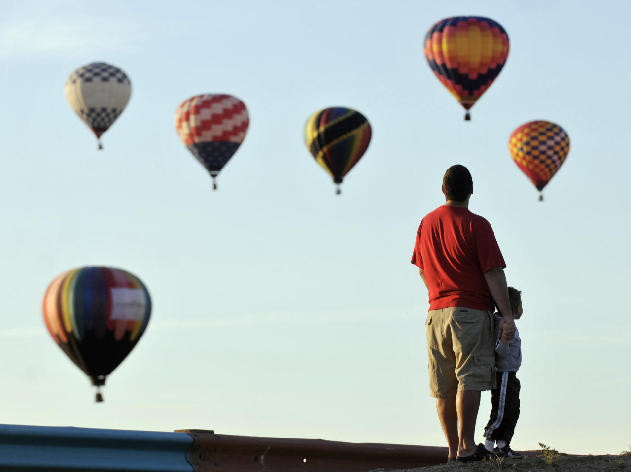 "Matt Brenner and his son Grey, 3, of Rio Rancho, watch mass ascension just north of Balloon Fiesta Park, on the first morning of the Albuquerque International Balloon Fiesta, Saturday, Oct. 2, 2010, in Albuquerque, N.M. ""There's lots of balloons,"" Grey said."