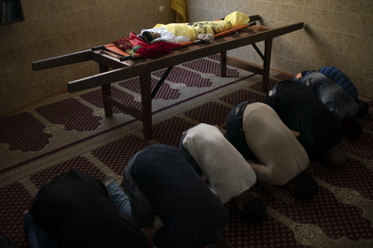 """In this Sept. 15, 2018 photo, Palestinians pray next to the body of 11-year-old Shady Abdel-al during his funeral in Beit Lahiya, northern Gaza Strip. Though the Health Ministry initially reported Abdel-al was shot by Israeli fire, the Israeli army claimed he was accidentally struck by a rock thrown by protesters. Two Gaza rights groups say he died after being hit """"with a solid object."""" (AP Photo/Felipe Dana)"""