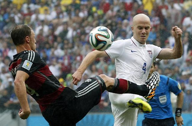 Germany's Benedikt Hoewedes, left, and United States' Michael Bradley challenge for the ball during the group G World Cup soccer match between the USA and Germany at the Arena Pernambuco in Recife, Brazil, Thursday, June 26, 2014. (AP Photo/Matthias Schrader)