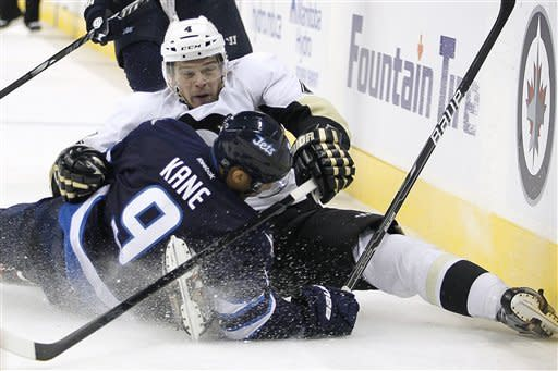 Pittsburgh Penguins defenseman Zbynek Michalek (4) and Winnipeg Jets forward Evander Kane (9) collide during second-period NHL hockey game action in Winnipeg, Manitoba, Friday, Dec. 23, 2011. (AP Photo/The Canadian Press, John Woods)