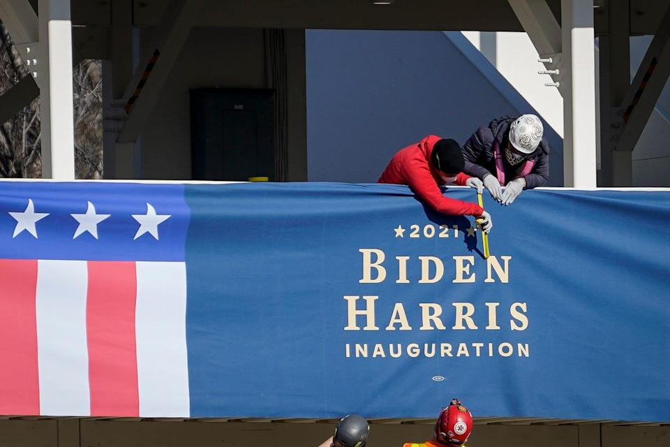 "WASHINGTON, DC - JANUARY 14: Workers put up ""Biden-Harris"" branded bunting on a press riser along the inaugural parade route near the White House on January 14, 2021 in Washington, DC. Thousands of National Guard troops have been activated to protect the nation's capital against threats surrounding President-elect Joe Biden's inauguration and to prevent a repeat of last weeks deadly insurrection at the U.S. Capitol. (Photo by Drew Angerer/Getty Images) ORG XMIT: 775611127 ORIG FILE ID: 1230585447"