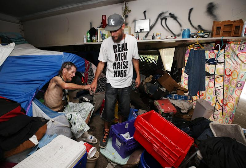 Brent Spradlin, left, fist bumps Jeff Gill, founder of Hip Hop Cares street outreach, as he took a break from packing his belongings in a homeless camp beneath the I-65 overpass at Brook and Breckinridge streets. The city has posted signs that they will be removing the camps starting July 12. July 10, 2019