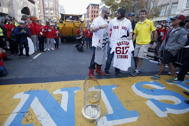 Boston Red Sox's Jonny Gomes, left, and Jarrod Saltalamacchia hold up baseball jerseys during a pause in their World Series victory rolling rally in Boston, Saturday, Nov. 2, 2013, to remember those affected by the Marathon bombing. They presented the jerseys to workers at two of the businesses at the bombing sites, including, second from right, Shane O'Hara and at far right, Dan Solo. (AP Photo/Elise Amendola)