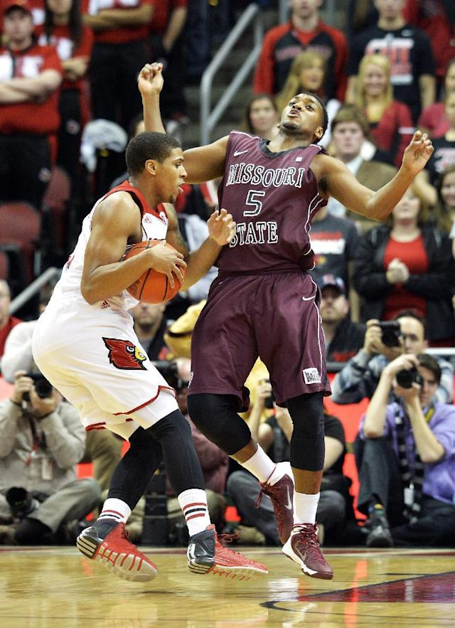 Louisville's Wayne Blackshear, left, charges into Missouri State's Michael Simpson during the first half of an NCAA college basketball game Tuesday, Dec. 17, 2013, in Louisville, Ky. (AP Photo/Timothy D. Easley)
