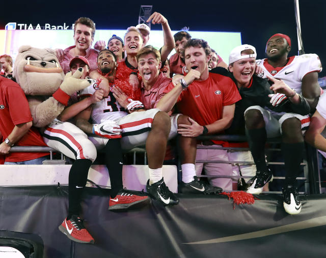 Georgia tailback Brian Herrien, center left, climbs into the stands to celebrate the team's 24-17 victory over Florida with the fans, mascot Hairy Dawg, left, and defensive back Richard LeCounte, right, after an NCAA college football game Saturday, Nov. 2, 2019, in Jacksonville, Fla. (Curtis Compton/Atlanta Journal Constitution via AP)