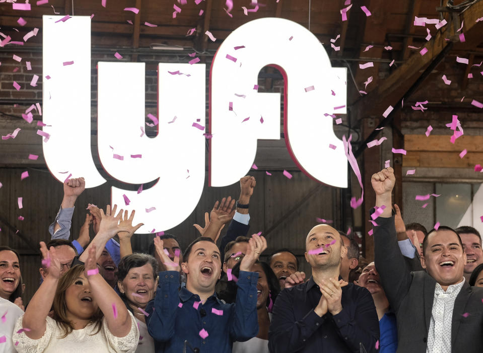 """Lyft co-founders John Zimmer, front second from left, and Logan Green, front second from right, cheer as they as they ring a ceremonial opening bell in Los Angeles, Friday, March 29, 2019. On Friday the San Francisco company's stock will begin trading on the Nasdaq exchange under the ticker symbol """"LYFT."""" (AP Photo/Ringo H.W. Chiu)"""