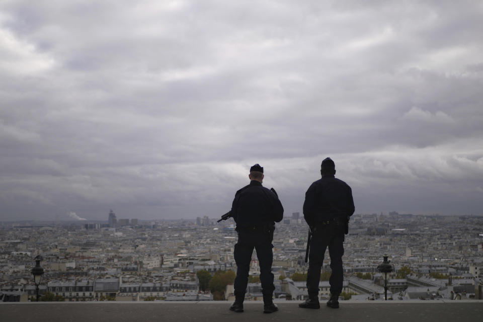 FILE - In this Oct. 30, 2020, file photo, police officers stand guard next to the Sacre Coeur basilica in Paris, following an attack at a church in the Mediterranean city of Nice. Scrubbing France clean of radicals and their breeding grounds is a priority cause of President Emmanuel Macron in a nation bloodied by terror attacks, including the beheading of a teacher outside his school in a Paris suburb followed by a deadly attack inside the basilica in Nice. (AP Photo/Thibault Camus)