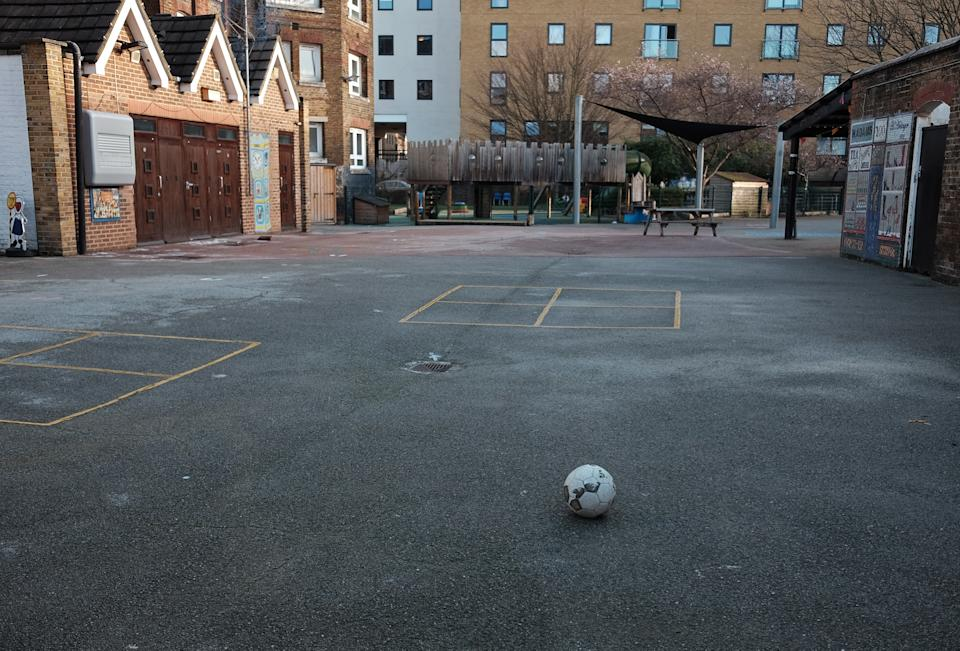A football lies on the empty playground of a primary school in east London, which has moved into the highest tier of coronavirus restrictions as a result of soaring case rates.