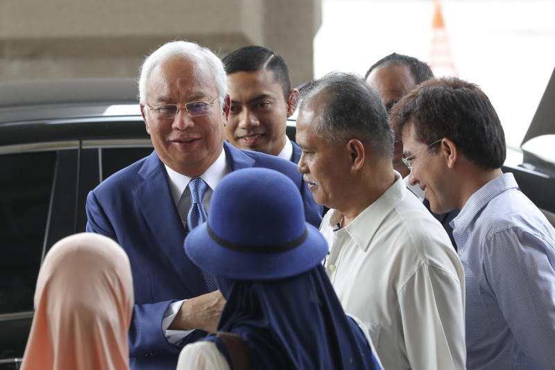 Former Malaysian Prime Minister Najib Razak, left, is greeted by supporters as he arrives at Kuala Lumpur High Court in Kuala Lumpur, Malaysia, Wednesday, Aug. 28, 2019. His second trial is due to begin Wednesday. (AP Photo/Vincent Thian)