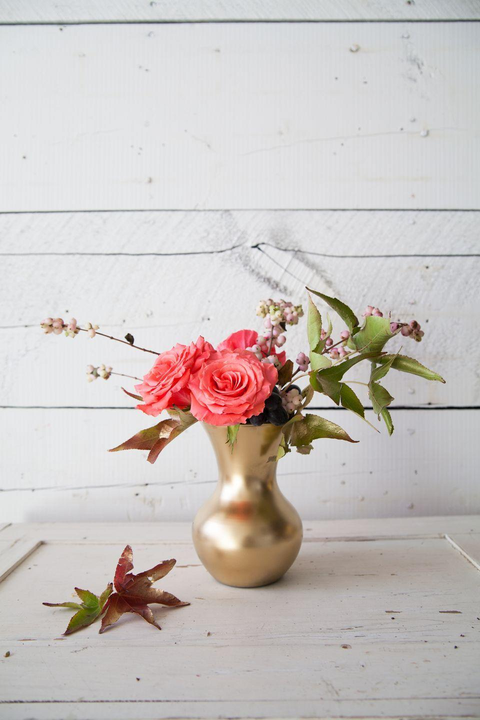"""<p>In this arrangement by <a href=""""http://www.themakerista.com/fresh-fall-florals-on-budget/"""" rel=""""nofollow noopener"""" target=""""_blank"""" data-ylk=""""slk:The Makerista"""" class=""""link rapid-noclick-resp"""">The Makerista</a>, sweetgum leaves have been gilded with <a href=""""https://www.elledecor.com/design-decorate/room-ideas/a7500/how-to-decorate-with-metallics/"""" rel=""""nofollow noopener"""" target=""""_blank"""" data-ylk=""""slk:metallic gold spray paint"""" class=""""link rapid-noclick-resp"""">metallic gold spray paint</a> and blended with snowberry branches, grapes, and roses.</p>"""