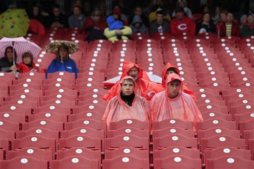 Fans sit in the stands during a rain delay before a baseball game between the Washington Nationals and the Cincinnati Reds, Sunday, May 13, 2012, in Cincinnati. (AP Photo/Al Behrman)