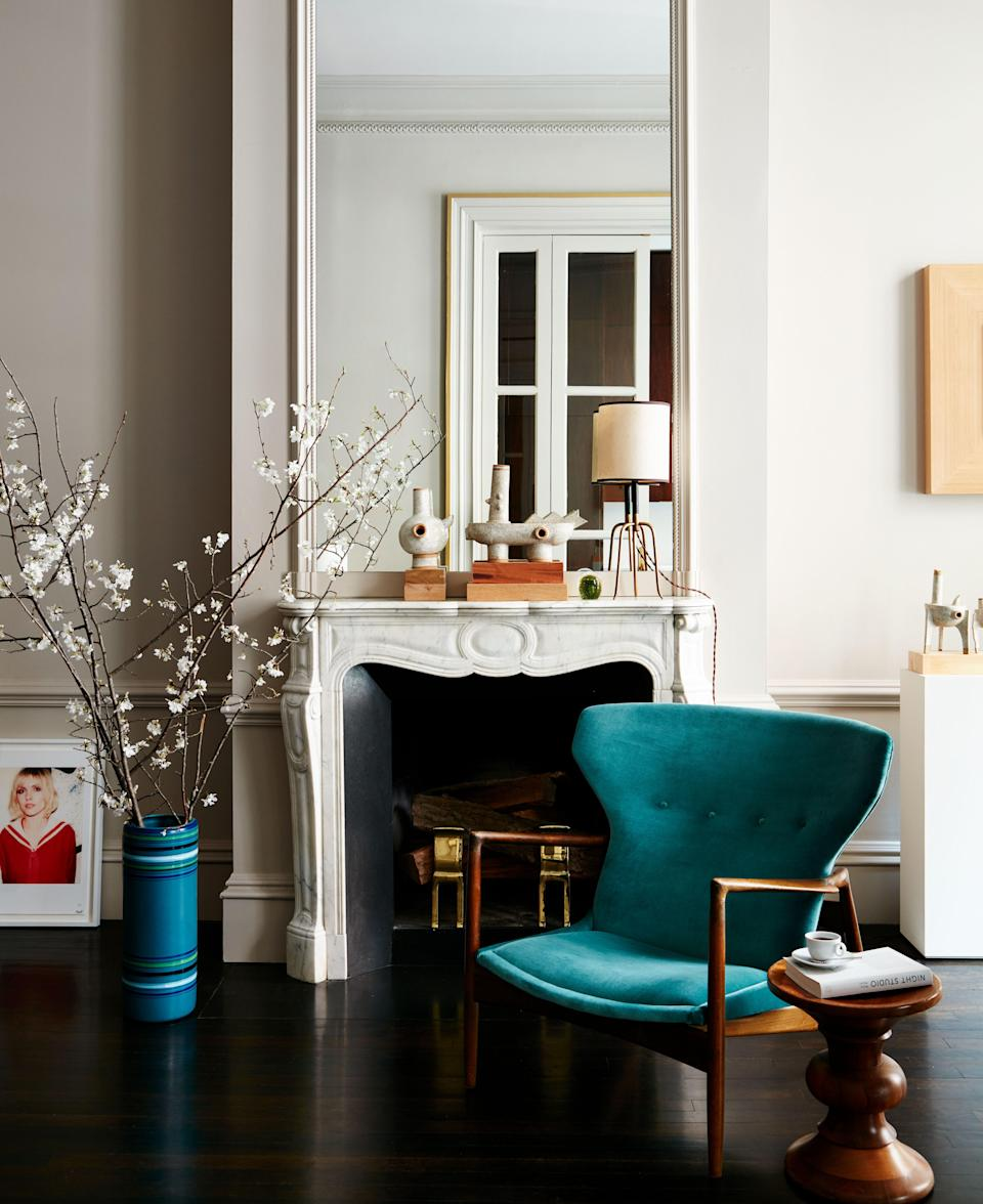 Beside a mantel in a corner of the dining room is a vintage Scandinavian lounge chair with a teak frame, upholstered in teal blue cashmere velvet from Pierre Frey.