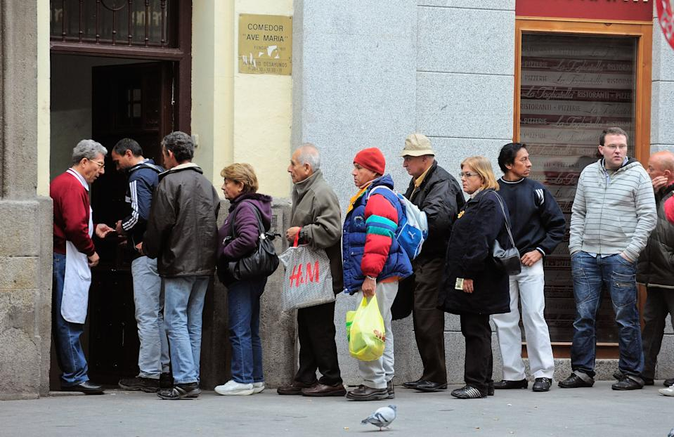 People queue up outside the Ave Maria charity food centre on November 9, 2011 in Madrid, Spain. Poor people and homeless are given a free breakfast at the centre run by the Fundacion Real Congregacion de Esclavos del Dulce Nombre de Maria. (Photo by Denis Doyle/Getty Images)