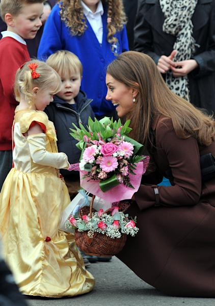 Britain's Catherine, Duchess of Cambridge receives flowers from 3-year old Isobelle Laursen, left, during her visit to Humberside Fire and Rescue Station in Grimsby, north Engalnd, Tuesday March 5, 2013. Her Royal Highness met many local people during her visit and people involved in a personal development course run by The Prince's Trust and delivered in partnership with Humberside Fire and Rescue Service. (AP Photo / Owen Humphreys) UNITED KINGDOM OUT - NO SALES - NO ARCHIVES