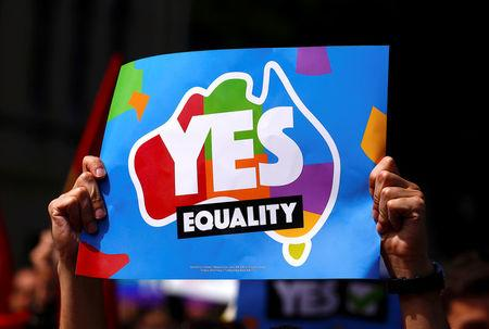 A marcher holds aloft a sign while participating in a marriage equality march in central Sydney
