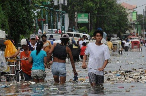 Residents wade through a flooded street filled with rubbish in the town of Navotas