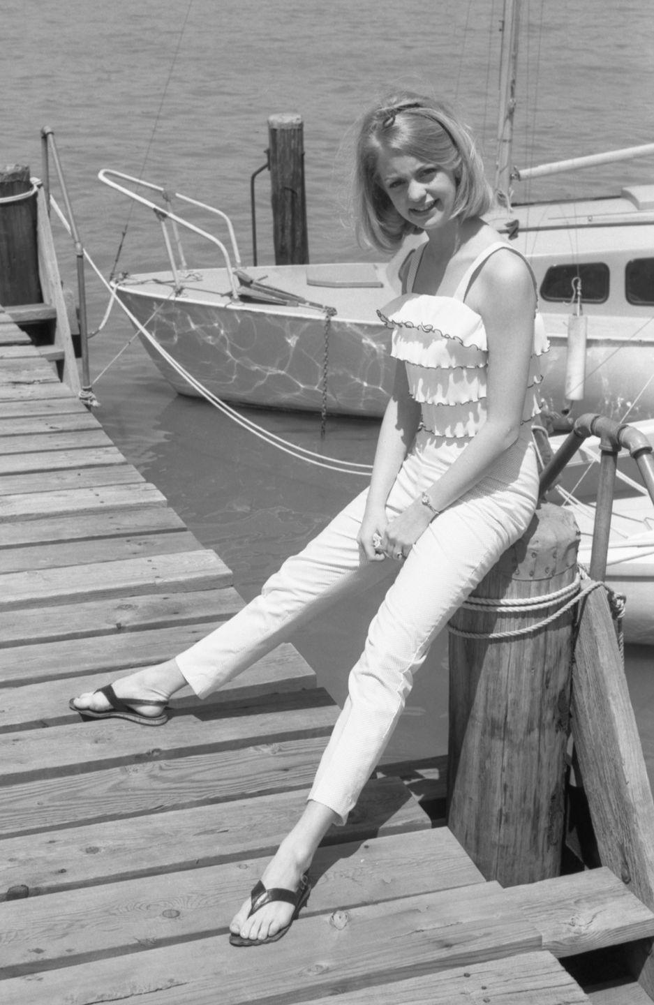 <p>Goldie Hawn gives the camera a smile while resting on the pillar of a dock. The actress looks ready for a summer day in a white ruffle tank top and white jeans. </p>