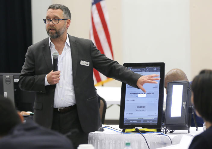 FILE - In this Thursday, Aug. 30, 2018 file photo, Eric Coomer from Dominion Voting demonstrates his company's touch screen tablet that includes a paper audit trail at the second meeting of Secretary of State Brian Kemp's Secure, Accessible & Fair Elections Commission in Grovetown, Ga. Eric Coomer, driven into hiding by death threats has filed a defamation lawsuit against President Donald Trump's campaign, two of its lawyers and some conservative media figures and outlets, Tuesday, Dec. 22, 2020. (Bob Andres/Atlanta Journal-Constitution via AP, File)
