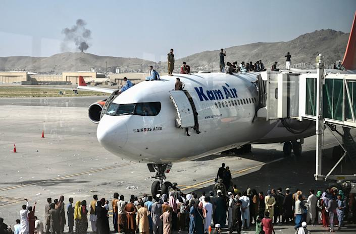 Afghan people climb atop a plane as they wait at the Kabul airport in Kabul on August 16, 2021, after a stunningly swift end to Afghanistan's 20-year war, as thousands of people mobbed the city's airport trying to flee the group's feared hardline brand of Islamist rule. (Wakil Kohsar/AFP via Getty Images)
