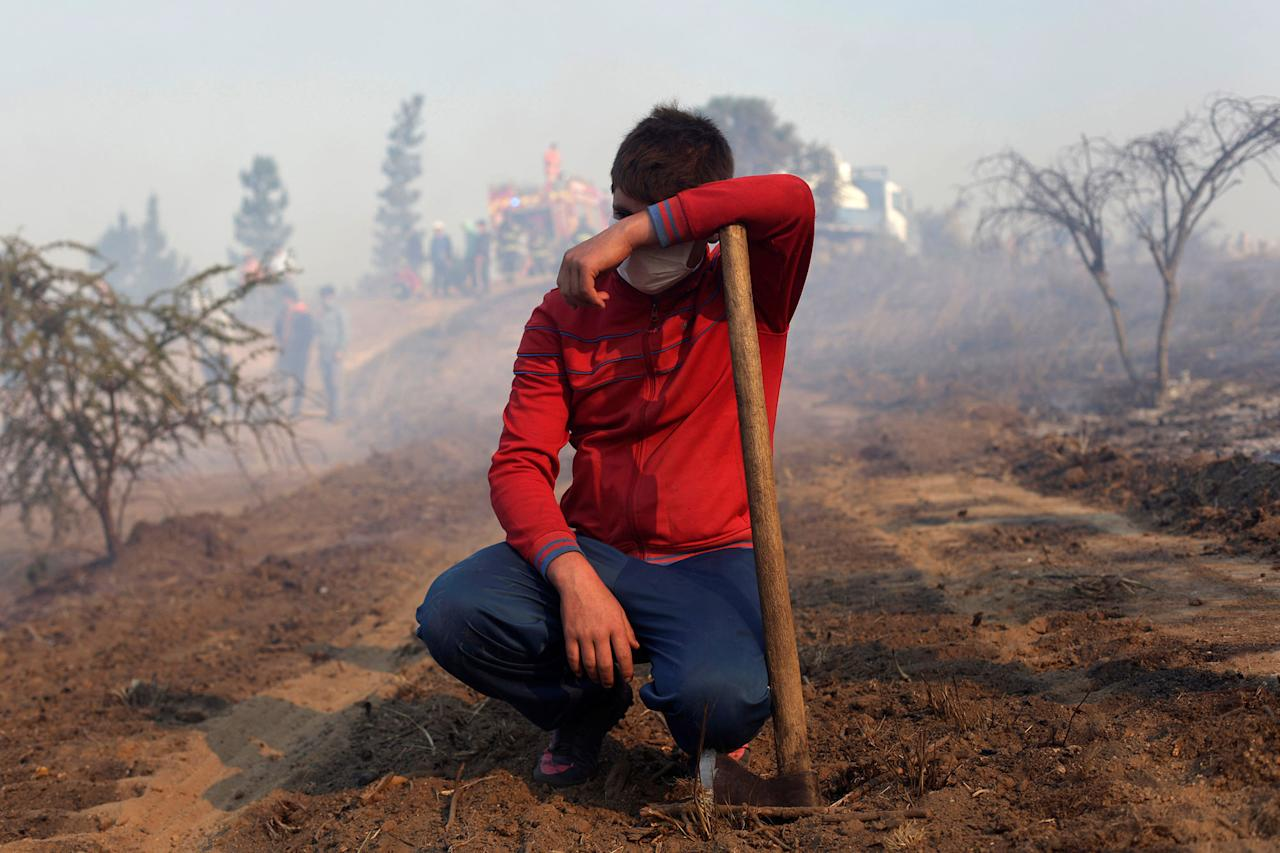 <p>A volunteer takes a break during wildfires in Chile's central-south regions, in Portezuelo, Chile on Jan. 30, 2017. (REUTERS/Juan Gonzalez) </p>