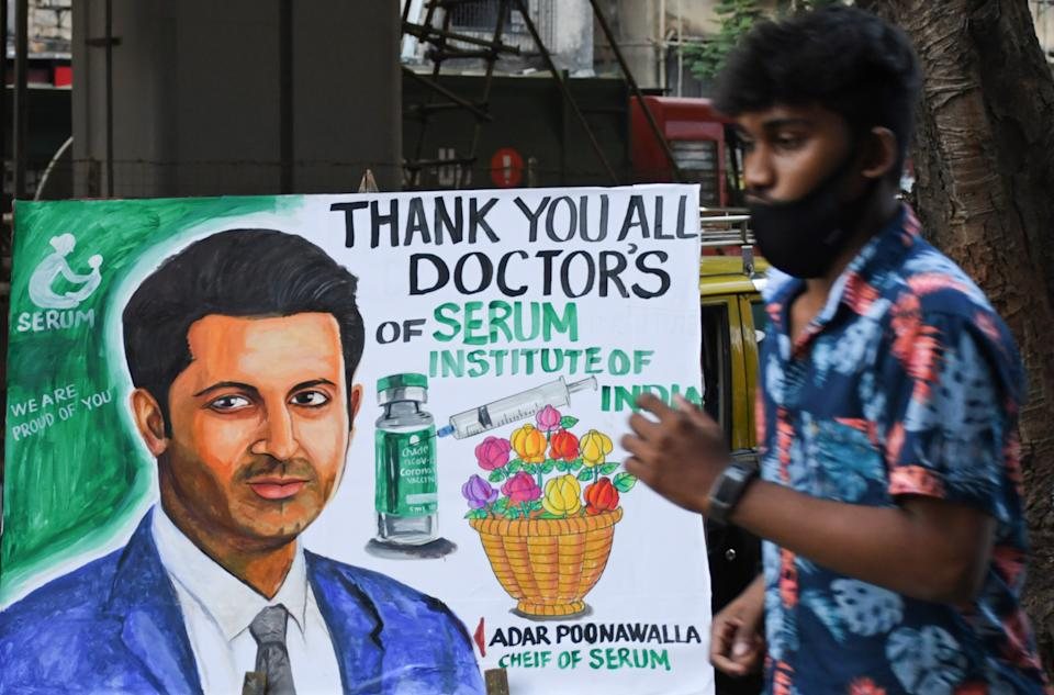 Mumbai, India: A man walks past a painting welcoming Covid-19 vaccination programme with a portrait of Adar Poonawalla, chief executive of the Serum Institute of India. Photo: Ashish Vaishnav/SOPA Images/LightRocket via Getty