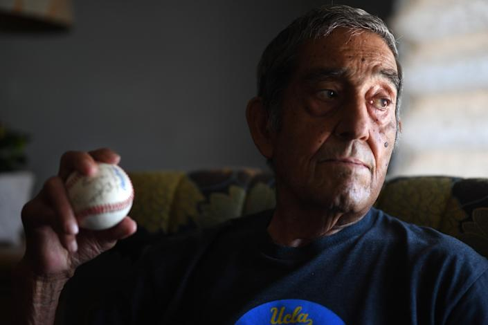 "Art Velarde holds an autographed baseball from his living teammates at his home in Hacienda Heights. <span class=""copyright"">(Wally Skalij / Los Angeles Times)</span>"