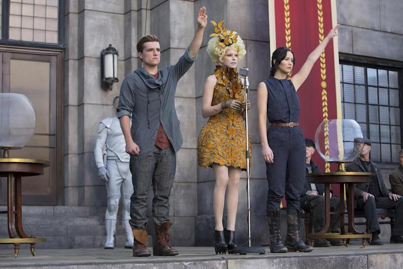 "This image released by Lionsgate shows Josh Hutcherson as Peeta Mellark, from left, Elizabeth Banks as Effie Trinket and Jennifer Lawrence as Katniss Everdeen in a scene from ""The Hunger Games: Catching Fire."" The movie opens in theaters Friday, Nov. 22, 2013, in what's expected to be one of the year's biggest box-office debuts. (AP Photo/Lionsgate, Murray Close)"