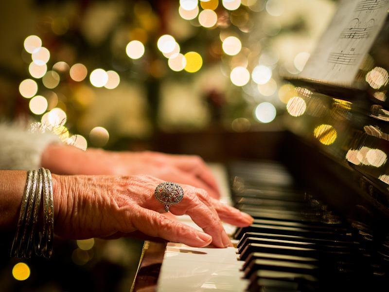 Close up of the hands of a woman playing Christmas carols on a piano