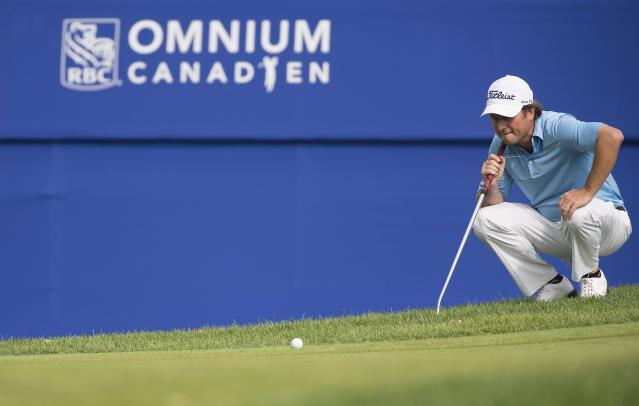 Tim Clark, of South Africa, lines up a putt on the 18th green during the third round of the Canadian Open golf championship at the Royal Montreal Golf Club in Montreal, Saturday, July 26, 2014. (AP Photo/The Canadian Press, Graham Hughes)