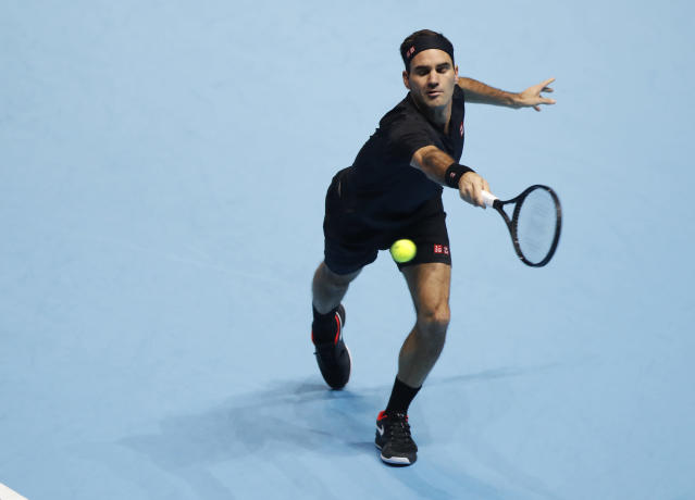 Switzerland's Roger Federer plays a return to Italy's Matteo Berrettini during their ATP World Tour Finals singles tennis match at the O2 Arena in London, Tuesday, Nov. 12, 2019. (AP Photo/Alastair Grant)