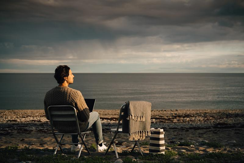 Thoughtful man using laptop while sitting at beach against cloudy sky