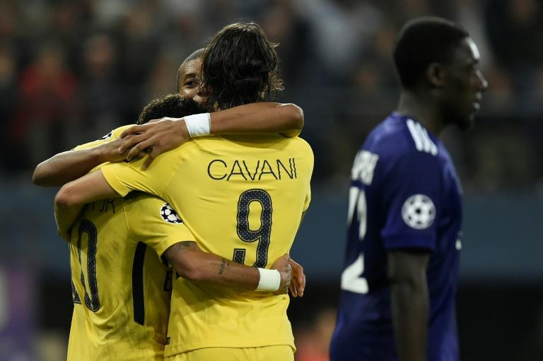 Paris Saint-Germain's Edinson Cavani (R) celebrates after scoring a goal with teammates Kylian Mbappe (C) and Neymar during their UEFA Champions League match against RSC Anderlecht in Brussels on October 18, 2017