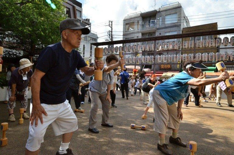 """Japanese pensioners work out in the grounds of a temple in Tokyo on September 17, 2012. Japan's finance minister Taro Aso has said the elderly should be allowed to """"hurry up and die"""" instead of costing the government money for end-of-life medical care"""